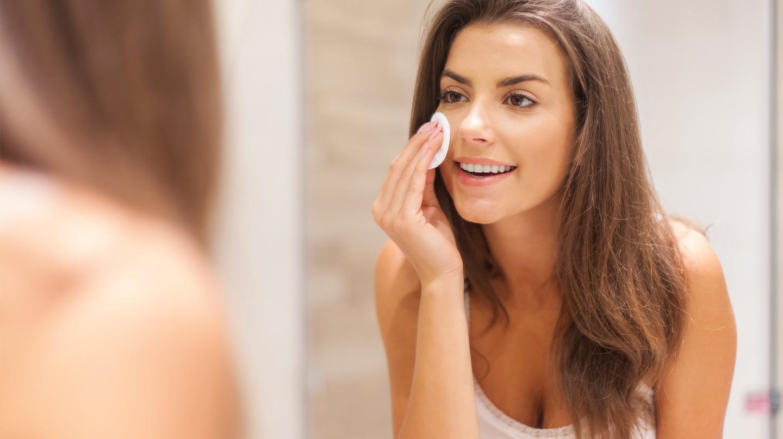 Beauty-Extras für die Haut: Junge Frau mit brünetten Haaren schaut in den Spiegel und hält ein Wattepad an die Wange.