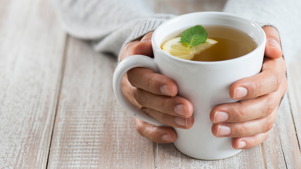 Ist Tee gesund? Zwei Hände halten weiße Tasse mit Tee.